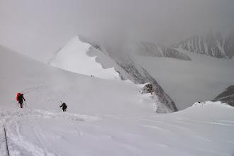"""Photo: Docieramy do naszego celu czyli przełęczy """"Windy corner"""" na wysokości 4040 m n.p.m. Tam wiatr jest jeszcze silniejszy a mróz jeszcze większy. Piotrek i Jacek szybko wykopali otwór w śniegu i przebili się przez lód aby zakopać wyniesione przez nas jedzenie na dalsze etapy wyprawy. W tym czasie ustawiłem GPS na drogę powrotną aby się zabezpieczyć przed zgubieniem trasy, gdyż widoczność i pogoda szybko się pogarszała. Spięci liną uciekamy na dół do obozu. Po drodze mijamy japończyka Massę i polską ekipę przenoszącą do góry cały obóz. Życzymy im powodzenia i podziwiamy ich wytrwałość, że robią to w tak trudnych warunkach pogodowych.  Na ostatnim odcinku, najbardziej stromym, przed samym obozem """"Motorcycle Hill"""" widoczność była tak tragiczna, że ledwo widziałem mocno jaskrawo-czerwony plecak Piotrka z odległości kilku metrów. Okulary miałem zaparowane, trasa po całym dniu była rozdeptana na kilka ścieżek, opady i wiatr przykryły ślady,ekran w GPS przymarzł i nie był czytelny.W efekcie idąc pierwszy zgubiłem drogę"""