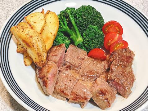 大皿に焼いてカットしたステーキ肉とポテト、ブロッコリーを盛りつけた画像