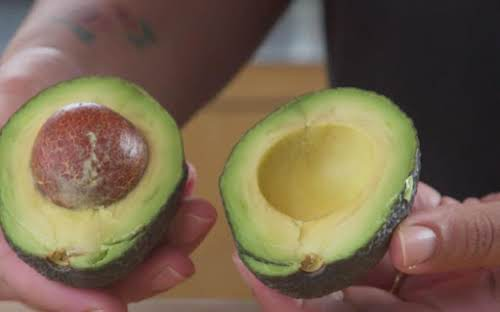 Once cut completely around, gently twist avocado and break in half.