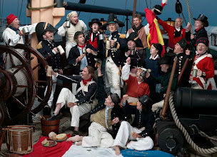 Photo: Nelson and his joyous crew celebrate victory over the French and Spanish fleets -with their spoils of war - a captured French flag by their feet and holding a captured Spanish flag