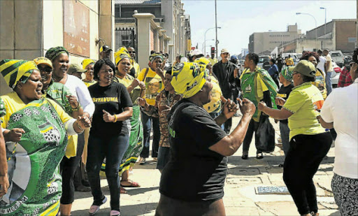 ENERGETIC: Supporters of suspended ANC regional secretary Pumlani Mkolo singing Mkolo singing outside the East London Magistrate's court ahead of his appearance with other accused for fraud relating to the Nelson Mandela funeral funds. Picture: ZWANGA MUKHUTHU