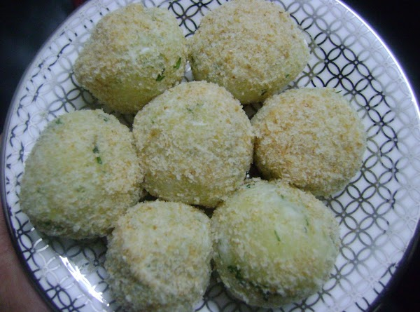Take the breadcrumbs in a flat plate.Dip the potato balls in the cornflour batter...