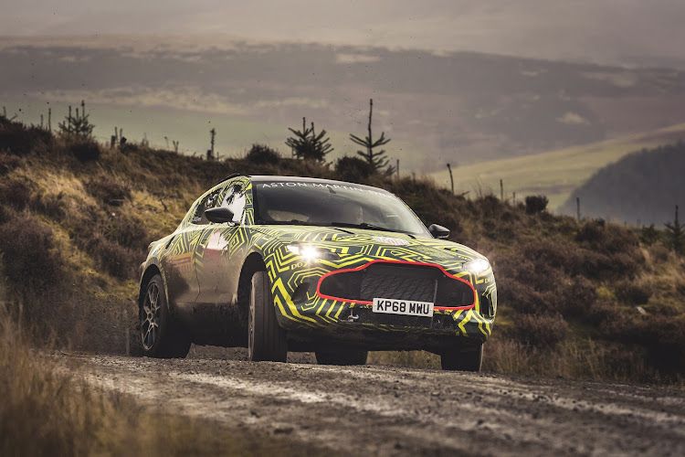 The camouflaged test mule of Aston Martin's new SUV is put through its paces on a rally stage. Picture: SUPPLIED