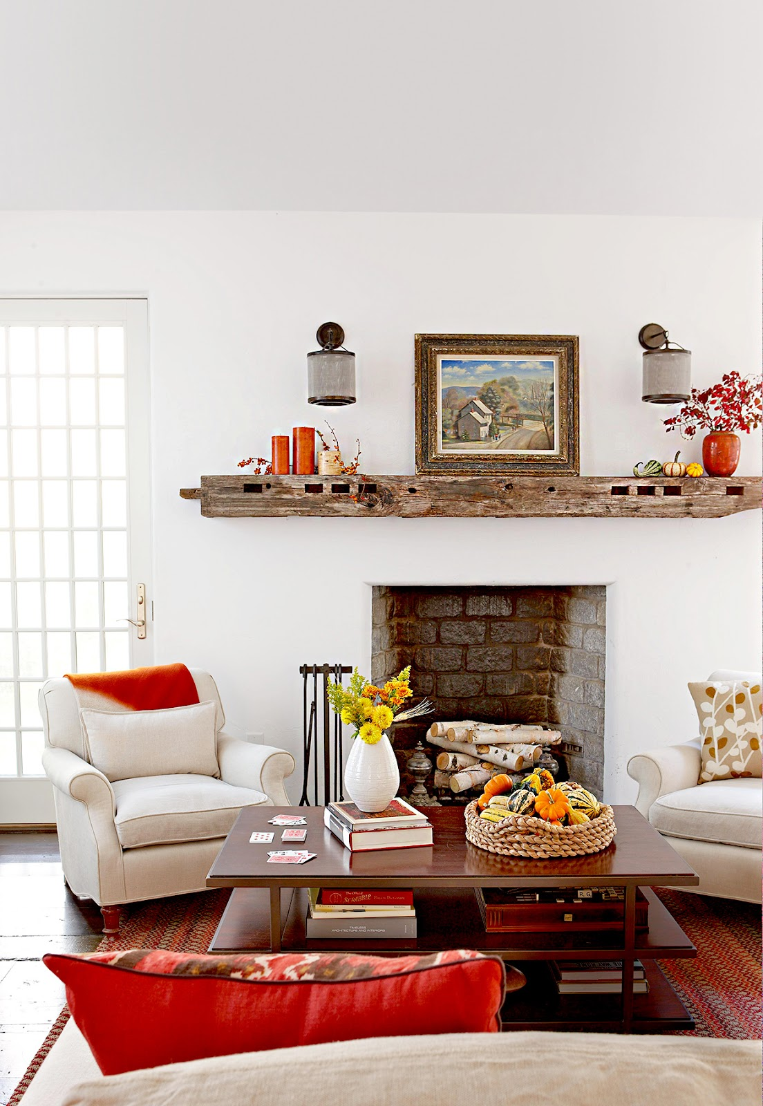 Living room setting in front of fireplace with fall decor.