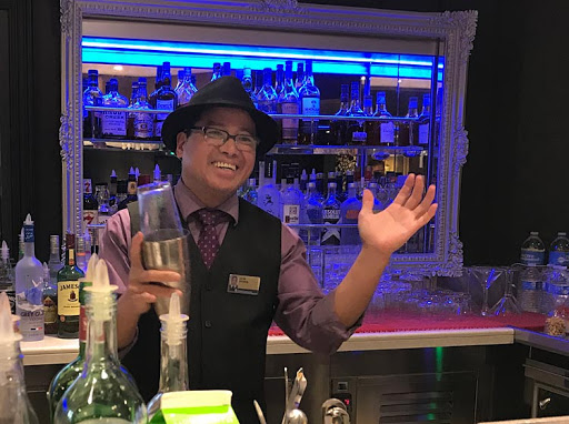 Barman Donato Sandiego entertains guests during a cocktail mixology class on ms Oosterdam.