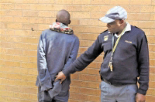 IN CUFFS: Inspector Moses Maphakela believes they have caught the man who has been terrorising Joburg motorists for more than a year. 20/05/09. Pic. Peter Mogaki. © Sowetan.