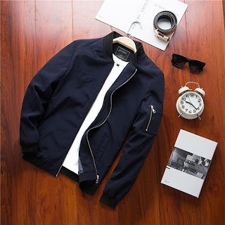 Plain navy bomber jacket with a black collar and a zipper pocket on left sleeve with a belt, a sunglasses, an alarm clock and a notebook on a wooden floor background