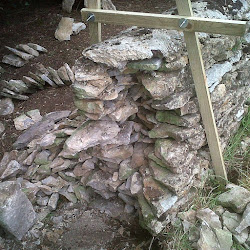 Customised frames of softwood can assist a dry stone waller hold up a field wall which would continue to fall when the gaps are being repaired