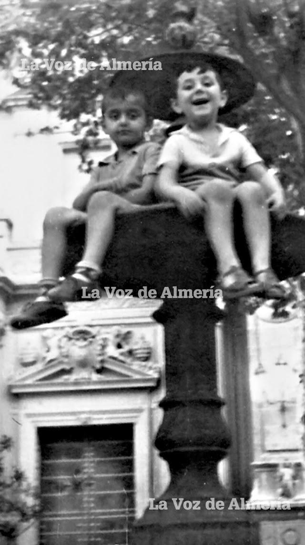 Dos niños subidos en la cumbre de la fuente de mármol dela Catedral, cuando estaba en el centro.