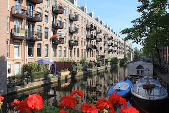 Photo: De achterzijde van het door bewonersactie geredde complex aan de Lijnbaansgracht. De koopwoningen werden verkocht met de leus: 'Schitterend wonen aan de Jordaanoever'. De bloembakken aan de brug worden door huurders uit de Willemsstraat verzorgd.