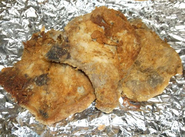 Place fried pork chops on cookie sheet and keep warm in oven while making...