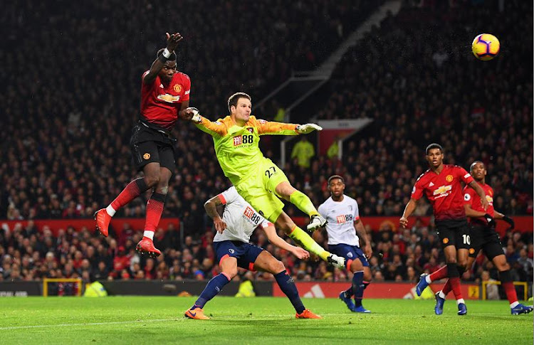 Manchester United star Paul Pogba (6) beats Bournemouth goalkeeper, Asmir Begovic to score his team's second goal during their Premier League match at Old Trafford on Sunday night. The Red Devils won the match 4-1.