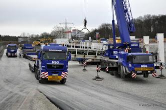 Photo: Hier sind drei MSG-Schwerlasttransporter und der Schwerlstkran von MSG zu sehen. Zwei weitere warten noch an der Baustellenzufahrt