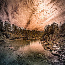 Lago delle Streghe (another sun) by Alessio Coluccio - Landscapes Mountains & Hills ( clouds, reflection, sky, nature, tree, waterscape, sunset, cloud, lake, landscape, rocks, sun )