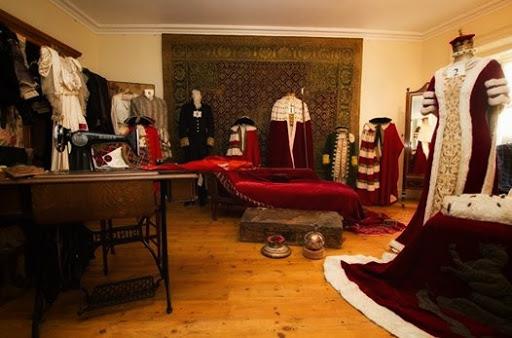 Habitacion de un castillo con articulos de costurera y trajes