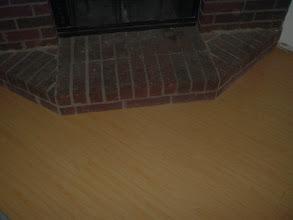 Photo: hardwood flooring under cut at fireplace, no molding needed.
