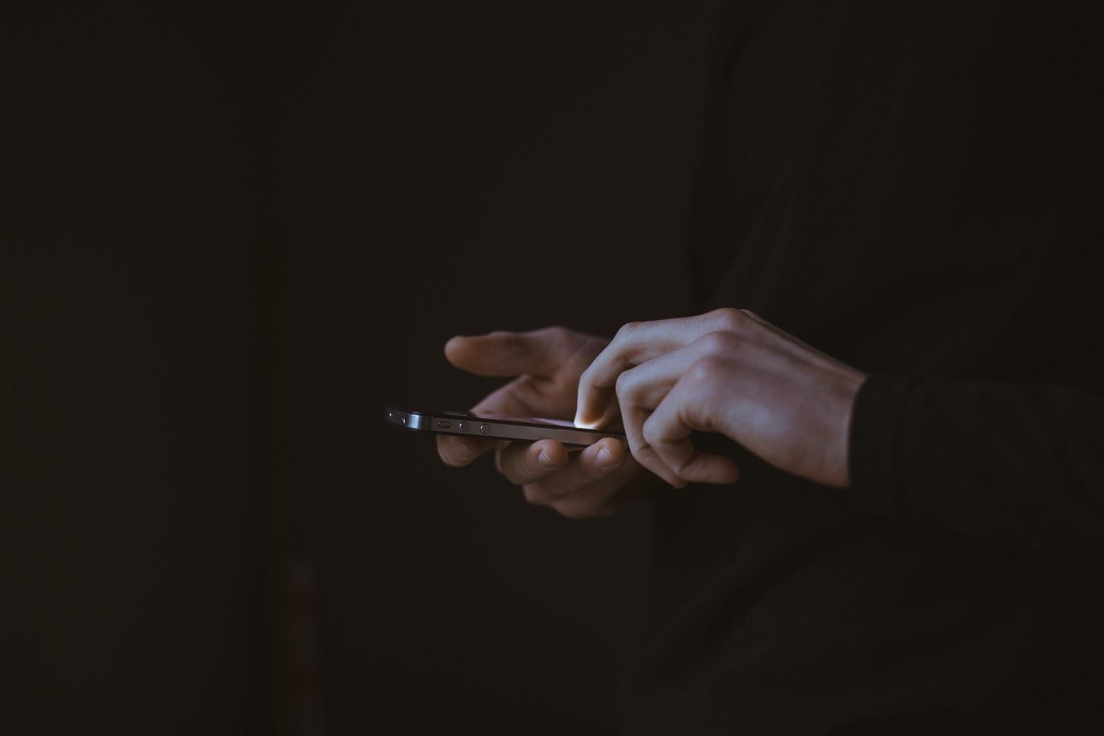 Pessoa mexendo no celular com as duas mãos para descobrir os requisito Uber.