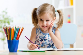 Little girl drawing with colored pencils
