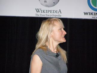 Γυναίκα που κάνει ομιλία. Στο φόντο φαίνονται μέρος από το λογότυπο της Wikipedia και του Wikimedia Mexico.