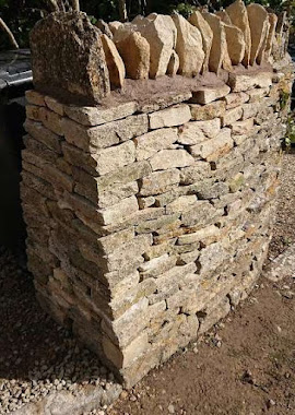 A Cotswold limestone dry stone wall reconstructed in Bibery