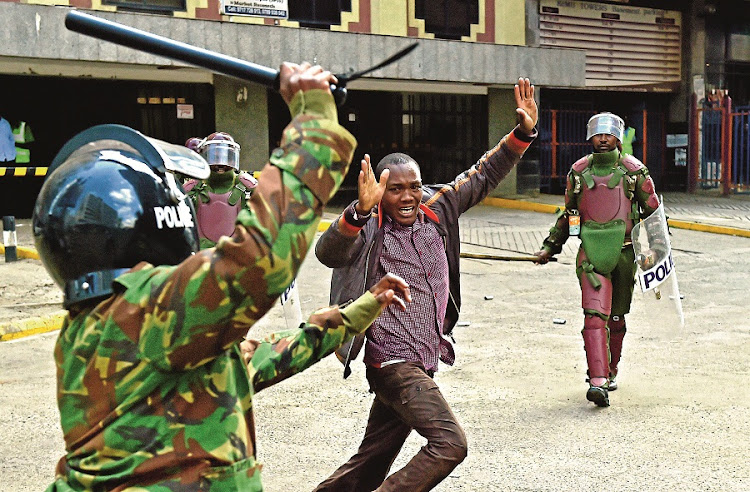 Kenyan riot police officers raise batons  over a man during a demonstration by Kenya's opposition supporters in Nairobi. Protesters  demand the removal of electoral commissioners, claiming they are biased. Picture: GALLO IMAGES/AFP/CARL DE SOUNZA