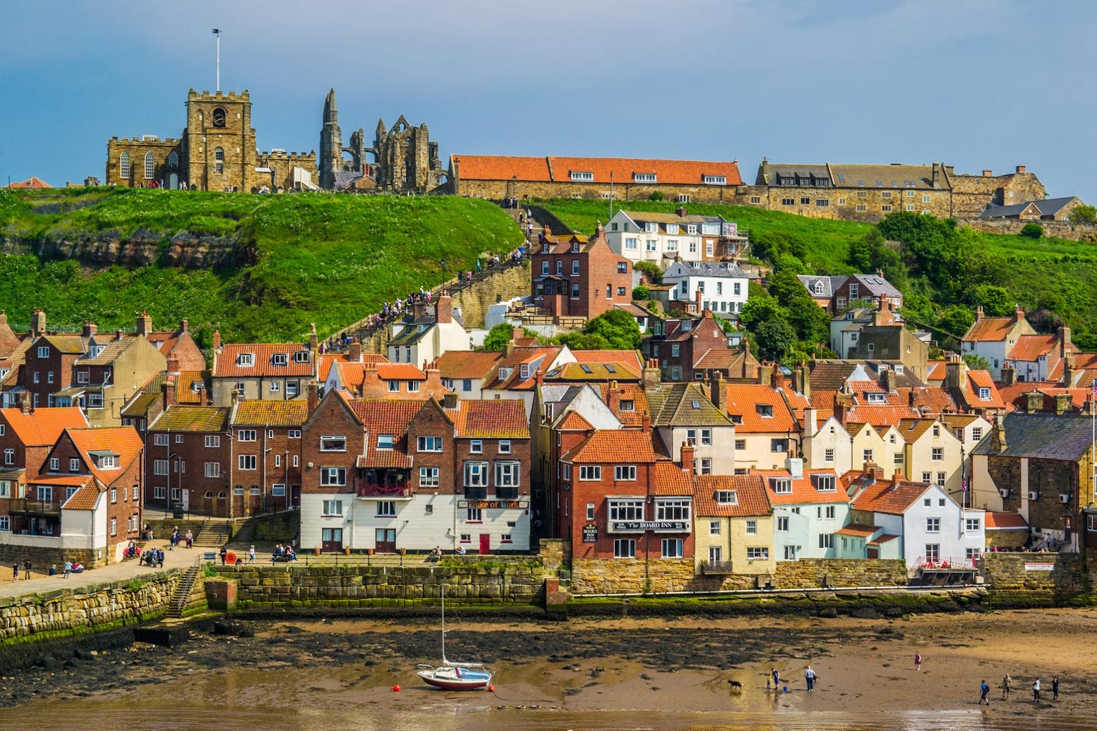 The town of Whitby exemplifies the village-on-the-coast vibe pretty well. The ruins of Whitby Abbey can be seen on the top right. Note how the buildings stack on top of the hill instead of carving straight into it.