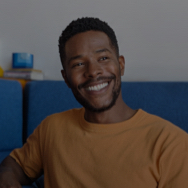 Man sitting indoors on a blue couch, smiling toward the camera