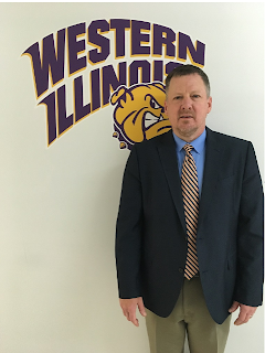 Image of a white male with light hair wearing a blue blazer, standing in front of the WIU logo