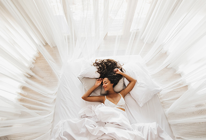 A happy woman sleeping in a white bed with white drapes all around her