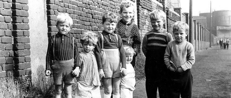 Gruppenfoto: Kinder vor einer Mauer.