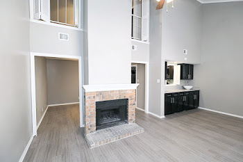 Living room with wood-inspired flooring, light gray walls, and a brick fireplace