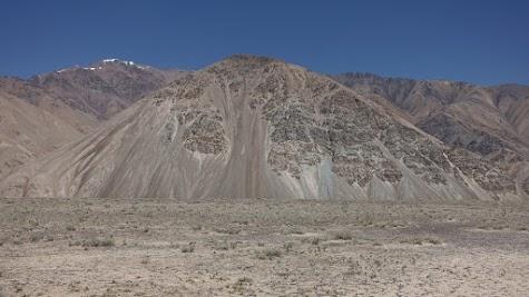 """Vielfarbiger Sand """"fließt"""" einen Hang hinab."""