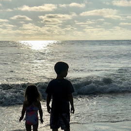 Siblings playing at the water's edge by Wendy Aull - Babies & Children Children Candids ( water's edge, siblings, waterscape, pacific ocean, sunset, silhouette, brother, sister,  )