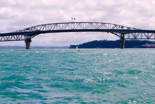 Kayaker-under-Auckland-Harbour-Bridge - A kayaker under Auckland Harbour Bridge in New Zealand.