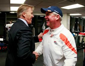 Photo: Executive Vice President of Football Operations John Elway congratulates Head Coach John Fox in the locker room after the win. Photo by Eric Lars Bakke / Denver Broncos