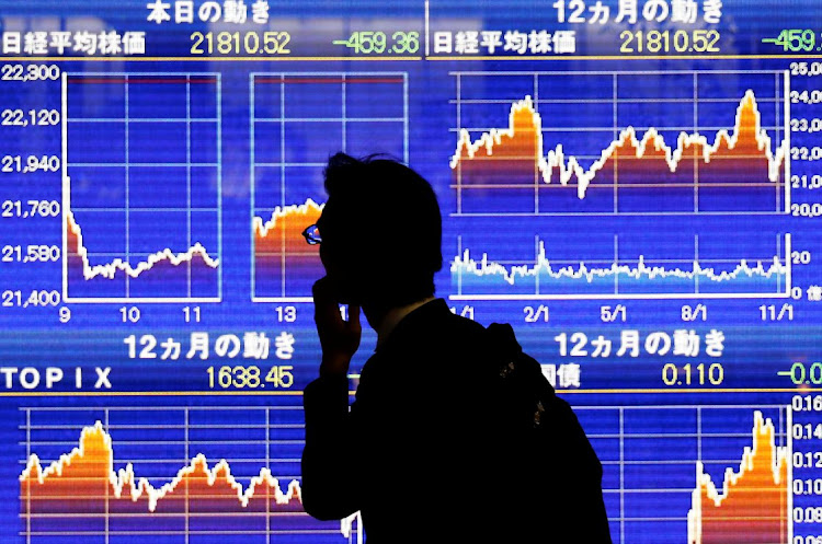 A man looks at an electronic stock quotation board showing Japan's Nikkei average outside a brokerage in Tokyo, Japan. File photo:REUTERS/TORU HANAI