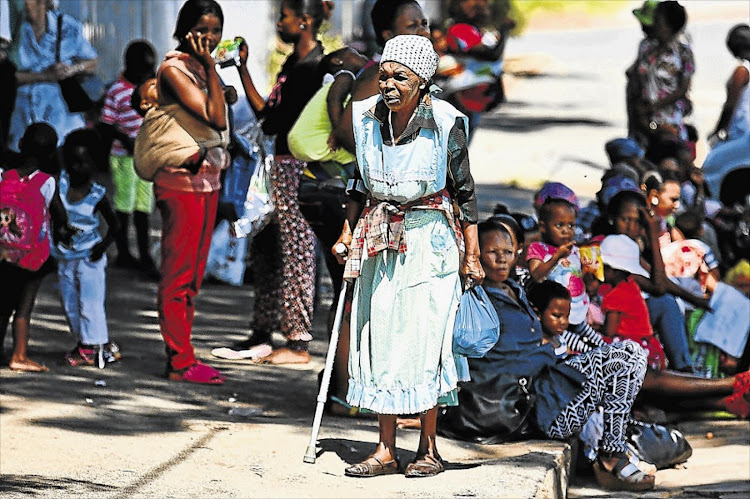 Beneficiaries queue for their grants at a payout point of the South African Social Security Agency. File photo: DAILY DISPATCH