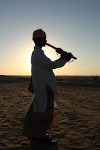 Photo: Silhoutte of a Sindhi man playing his instrument at Sam