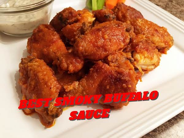 Chicken Wings On A White Plate With Dipping Sauce In A Glass Dish With Veggies In The Background.
