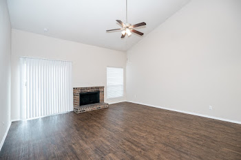 Manchester floorplan's spacious living area with tall ceiling, wood-style flooring, and brick fireplace