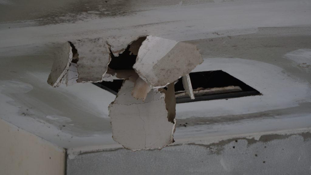 gros trous dans un plafond d'une maison de montréal avec des bouts de panneau brisés