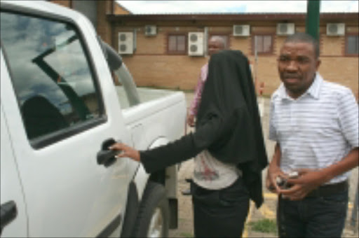 COVERING UP: The organised crime unit whisk away one of the Mbombela municipality officials accused, among other charges, of issuing motor vehicle licences for unroadworthy cars in Nelspruit, Mpumalanga. The two men appeared in court last week on fraud charges. Pic. Andrew Hlongwane. 02/2008. © Sowetan.