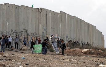 Photo: Palestinian youth hurl stones towards Israeli soldiers at the Qalandia checkpoint, in the Israeli occupied West Bank.