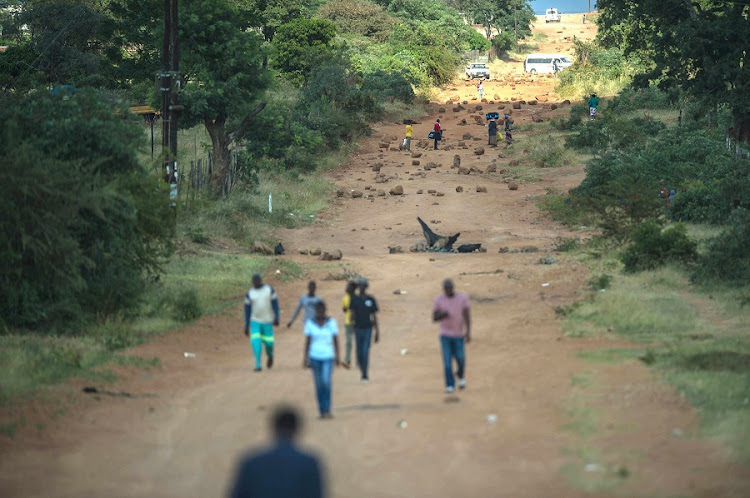 Residents walk along a road blocked with debris after schools were torched by residents in Vuwani. Picture: AFP PHOTO/MUJAHID SAFODIEN