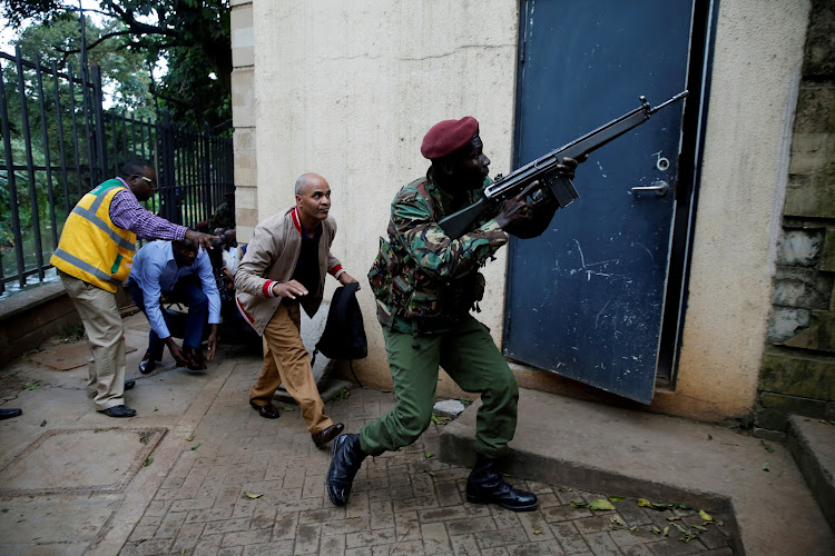 A member of security forces keeps guard as people are evacuated at the scene where explosions and gunshots were heard at the Dusit hotel compound, in Nairobi, Kenya, on January 15 2019.