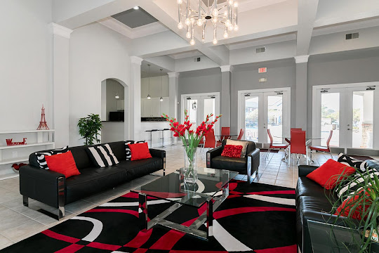 Community clubhouse seating area with plush chairs and couches, modern hanging light fixture, and red decorative accents