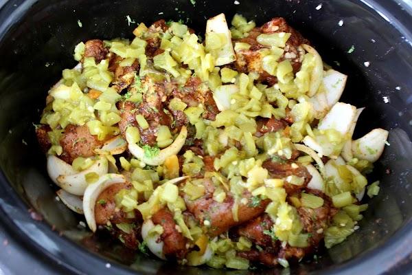 Chicken, onion, and garlic in a Crock Pot.