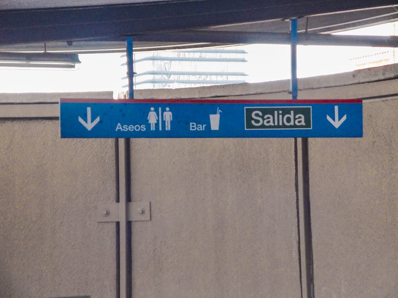 A sign showing the direction of the bathrooms, bar, and exit