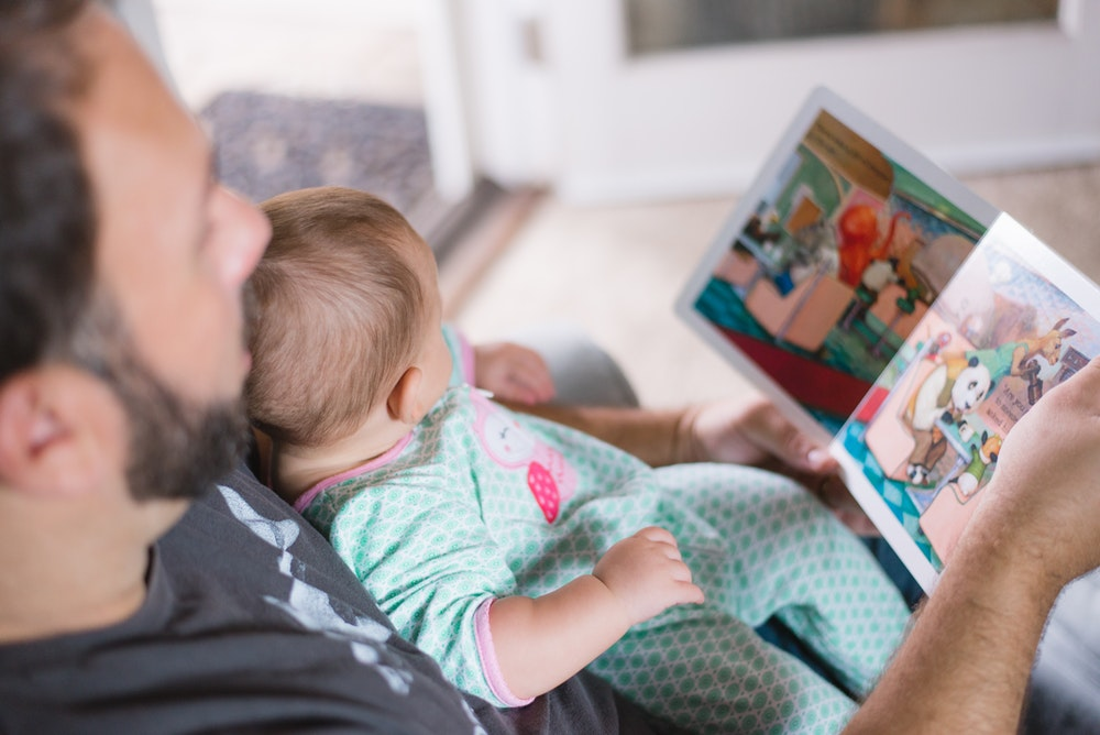 A baby sitting with her father while looking at a kids book.