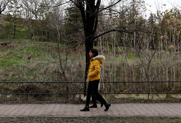 Azam Jangravi and her daughter walk along a park, at the unknown location, February 7, 2019.